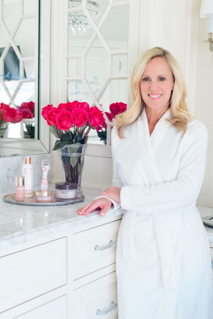 woman in white bathrobe with red roses