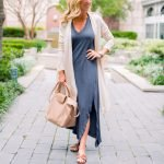 woman in blue dress with white jacket on brick walkway